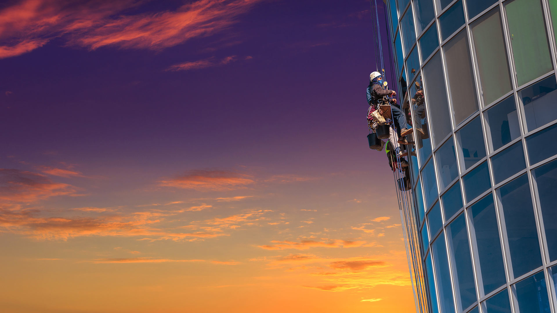 Person scaling a high rise building